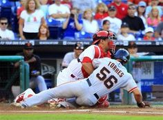San Francisco Giants' Andres Torres scores against Philadelphia Phillies catcher Carlos Ruiz on a sacrifice fly by Pablo Sandoval during the first inning of a baseball game Tuesday, July 30, 2013, in Philadelphia. (AP Photo/Tom Mihalek)