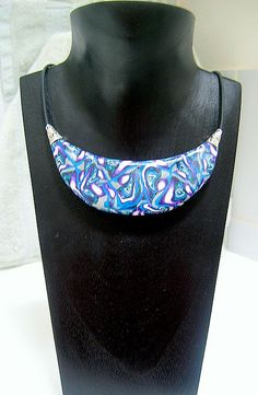 https://flic.kr/p/3nNtUx | Large Crescent Pendant | This is a large(ish) looks much bigger on the display than on the neck) polymer clay pendant made using a swirled blue, purple, while and silver cane. It is accented with silver bead caps and strung on black rubber cord.  cgi.ebay.com.au/OOAK-Polymer-Clay-Pendant-necklace-Hand-c...