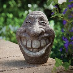 """Big Stone Smiley Face, Item # 46523.  $12.99.  Bring some unexpected humor into your yard or garden with our wide grinning friend. Cast in lightweight weather resistant polyresin and painted to replicate a real rock, he will encourage smiles and laughter when discovered. Measures 8"""" tall x 6"""" wide."""