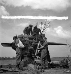 Canadian Film and Photo Unit personnel with a captured German 88mm anti-aircraft gun near Bayeux, France, 26 August 1944. August 26, 1944 Library and Archives Canada MIKAN 3396244