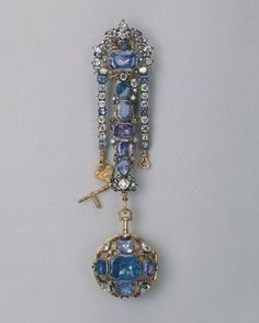 Watch on a chatelaine, by Charles Carbier, English, c. 1720. Chased and engraved; made of gold, silver, sapphires, enamel, glass, and metal alloys. From the Hermitage Museum.