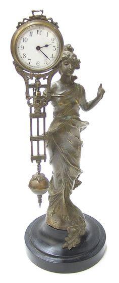 Art Nouveau circa 1930, woman holding wind-up pendulum clock.