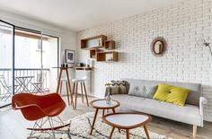 small interior with retro furniture and pastel colors including Eames RAR chair, moroccan rug