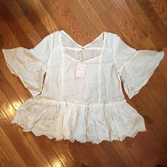NWT  Free People - Ivory Flowy Top Beautiful flowy top. Never worn - comes with tags. Features lace down the front and embroidery along the bottoms. Size small but could fit like a medium. Meant to be loose. Free People Tops Blouses
