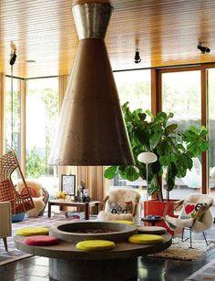 Junto al icono de los 50, la chimenea metálica redonda,  un sillón colgante vintage.