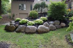 "Others. Boulders need to be done with an artist.  Fit them like a ""glove"".  Keep your height the same.  You will have to dig some in and raise others.  Use conifers to cascade over the wall to soften the stone. Retaining wall, berm, landscaping."