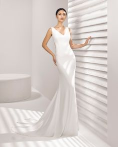 Simple and elegant mermaid-style wedding dress that will cause a sensation when you turn to reveal the elegantly seductive lace back. 2018 Rosa Clará Collection.