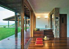 Parte da área de lazer, o spa se integra ao deck externo. Atrás da banheira, um vidro isola a sauna. Assoalho de réguas de cumaru e almofadas no chão da Futon Company.