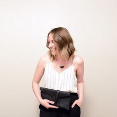 Available in a buttery smooth black leather, The Stitch & Shutter Leather Wrap Clutch is perfect dressed up or down- paired with leather or lace. #madeinusa #americanmade #colorado #handbag #clutch #leathergoods #leatherbag #handmade #wrapclutch #leatherclutch