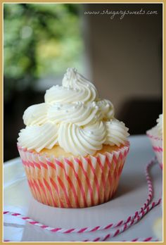 I like the piping on these | Shugary Sweets: Almond Wedding Cake Cupcakes with Raspberry Filling