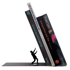 This poor bloke was just minding his own business when the weight of words began to topple toward him. While the fate of this silhouetted figure hangs in the balance, the sturdy metal construction of the Falling Bookend means you'll never have to worry about the fate of your books. #colossal