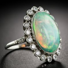 Opal and Diamond Platinum Ring.  This beautiful jewel features a vibrant 7 carat oval opal glowing with a painter's palette of blue, green, and fiery orange flashes floating within a glittering frame of 3/4 of a carat of sparkling round brilliant-cut diamonds. Handcrafted in lustrous platinum, with lovely details like a lacy gallery, bead-set diamond shoulders and delicate milgrain engraving. In a finger size 6 3/4.