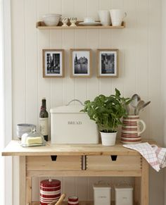 Hanging photos above a wooden display trolley from Ikea