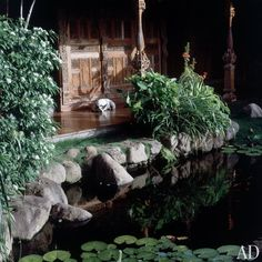 """""""By the stone entrance is a 19th-century teak carved wall known as a 'pateanaring panel,' which is an internal wall from a traditional house in central Java,"""" explains Garland. (David Bowie's House on the Island of Mustique)"""