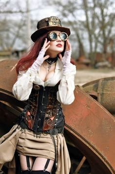 Steampunk Redhead in Neutral Color Palette (white, black, brown, tan, gold) with stockings and garters, corset, skirt and blouse. Accessories include hat, goggles, pocketwatch, eyeglasses, jewelry (rings and choker necklace) - For costume tutorials, clothing guide, fashion inspiration photo gallery, calendar of Steampunk events, & more, visit SteampunkFashionGuide.com