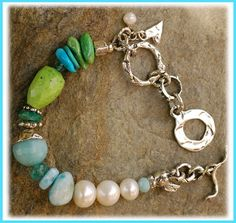 Handcrafted sterling silver,  large Freshwater Pearls, Amazonite, Larimar,  Apatite, Primavera Stone, Sleeping Beauty Turquoise and Gaspeite  all representing shades of the sea.    Bracelet measures slightly over 7.5 inches  fits a wrist size 6.5 perfect.