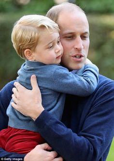 Prince George cuddles with Prince William during a children's party at Government House - Sept. 2016.
