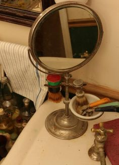 "19th/20th C pedestal shaving mirror with a beveled glass edge, brush holders and milk glass dish 16""T, Barbasol spray lather shave, Kep-Rite hair dress, Hair gloss, Pinaud clubman aftershave, and other grooming products in glass bottles."