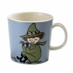 This classic blue Moomin mug by Arabia from 2002 features Snufkin fishing and playing the flute. It's artfully illustrated by Arabia artist Tove Slotte-Elevant and the illustration can be seen in the original picture book Who Will Comfort Toffle?You collection of Moomin mugs will not be complete without this wonderful piece. Also see the other parts of the ceramic Snufkin series.