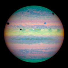 Hubble Spots Rare Triple Eclipse On Jupiter - Io, Ganymede and Callisto cast their shadows on Jupiter. Io - white spot above image center / shadow left of white spot : Ganymede - blue spot upper right / shadow far left edge : Callisto - out of frame at right / shadow upper right edge