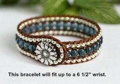 This beaded leather cuff features 3 rows of glass beads and genuine leather. Metallic silver seed beads surround a center row of denim blue. Each bead is hand stitched between rows of distressed light brown leather. For a touch of country charm this bracelet fastens easily with a
