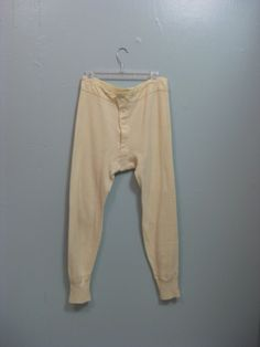 This is a pair of Edwardian mens long johns. Theyre a cream colored thick cotton. They button up the front and tie at the back. The condition is very good, but there are some faint spots on the front and one darker one on the back of the calf. Measurements in inches: waist 32, hips 38,