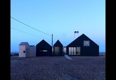 """""""The blackness of Dungeness can be seen in the variety of sheds, huts, garages, storage containers and boats. The lighthouse, Derek Jarman's house, Garage Cottage, Simon Condor's black rubber house and the abandoned boats all share the common black aesthetic.  """"Traditionally people on this part of the coast used tar paper and pine tar as a protective coating to shacks and cottages. It was originally used as a water repellent to coat fishing boats or nets and thBuilding study 