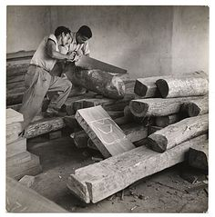 """Citation: Two individuals select and saw wood for carvings from the """"Estudios de Artes Manuales,"""" ca. 1940 / William Vandivert, photographer. Lawrence and Barbara Fleischman papers, Archives of American Art, Smithsonian Institution."""