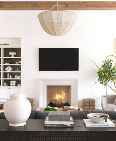 Exposed wood beam + wood beam detail + living room design + sofa table + sofa table styling + book stack + white vase + woven lighting + white fireplace + TV above fireplace + built-in shelving Home Living Room, Living Room Designs, Living Room Decor, Living Spaces, White Family Rooms, Sweet Home, Beautiful Interior Design, Family Room Design, Living Room Inspiration