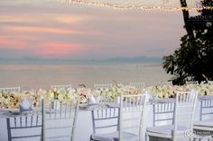 A beautiful table runner of fresh flowers and candles and a backdrop of the Ocean