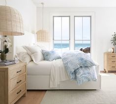 Neutral & Blue Coastal Palm Bedroom Shop the look of these soothing palmy bedroom. Neutral coastal bedroom with wood furnishings, wicker pendant lights and breezy blue bedding with a palm leaf motif. Coastal Master Bedroom, Coastal Bedrooms, Home Bedroom, Bedroom Furniture, Bedroom Decor, Pottery Barn Bedrooms, Airy Bedroom, Bedroom Neutral, Furniture Decor