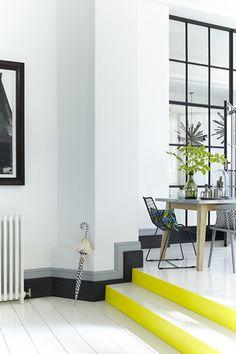 Peinture salle à manger : murs gris Flint (236), plinthes bicolore Lampe Black (228) et gris Sarcelle (226) de Little Greene. Contremarches peintes en jaune vif