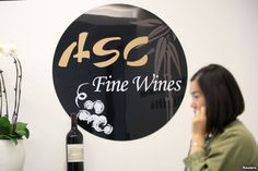 A woman walks past a sign of ASC Fine Wines at its headquarters in Shanghai, China,