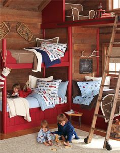 We layered three beds in a palette of blue, brown and white to create distinct yet coordinating sleep spaces. A ladder and a cozy chair transformed a loft into a cozy, private reading nook. The palette based in natural wood tones with red accents, as well as accessories including a set of antlers and snowshoes, give the room a rustic-cabin-in-the-woods feel.
