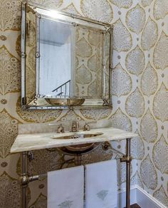 Chic powder room features walls clad in Galbraith and Paul Lotus Wallpaper lined with a square beveled mirror over a 2-leg washstand topped with onyx fitted with a stainless steel sink.