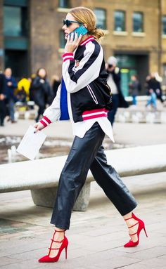 Olivia Palermo wears black leather pants, a white sweater, a black varsity bomber jacket, and red pointed toe heels.