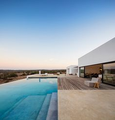 the composition of stark white volumes by colectivarquitectura serve as a spacious home nestled in the dusty landscape.