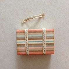 Use the remaining strip of pattern paper, make a small handle like this...