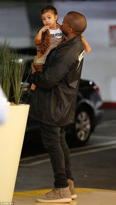 He seems like a great dad: West held onto his little girl with both arms
