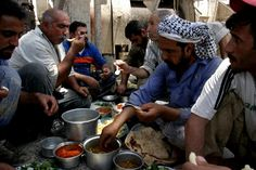 Description: The drilling crew eating lunch together in the Arab style, sitting around the bowls and pots, and sharing what they have.  Photo Credit: Bacon