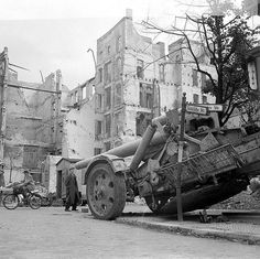Civilian looks over an abandoned German 210-mm heavy field howitzer Mrs.18 (21 cm Mörser 18) on a war-torn Berlin street.