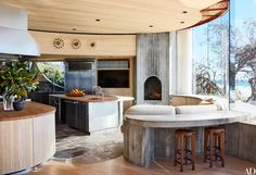 A new stainless steel island and butcher-block countertops blend with the kitchen's original concrete counter, Yosemite-slate floor, and fireplace/grill; the curtain panel is of a Cowtan & Tout fabric, the clocks are by George Nelson, the sink fittings are by Kallista, and the barstools are vintage Pierre Jeanneret.