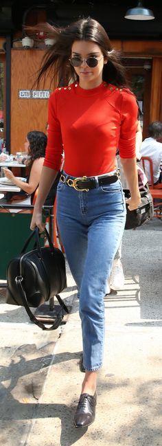Kendall Jenner in high waisted jeans embellished with a statement belt, a bright three quarter sleeve shirt, oxfords, and a leather satchel.