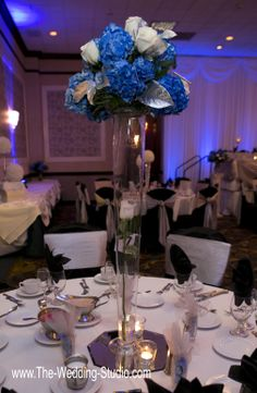Wedding Centerpiece: Tall clear vase topped with blue & white flowers and silver leaves at The Mirage Banquets in Schiller Park. Photographed by The Wedding Studio, Schaumburg IL