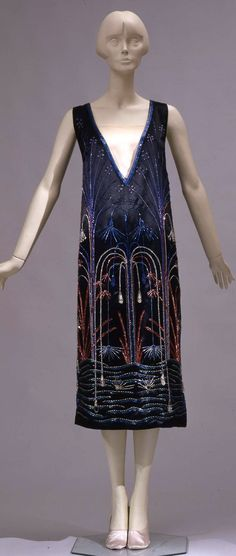 Evening dress, Sartoria Ventura, Rome (?), ca. 1925. Short sleeveless dress in black silk satin, embroidered with glass straws in different colors. The embroidery resembles plants falling into the water, looking like fireworks. Photo: Gabinetto fotografico SBAS, Antonio Quattrone, Marcello Bertoni. Collection Galleria del Costume di Palazzo Pitti via Europeana Fashions