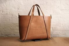 WholeCut Type II by Charlie Borrow. Hand stitched leather bag in Russet (un-dyed) bridle leather from Baker's Tannery in Devon. The body is cut from a single piece of leather. Image via Charlie Borrow
