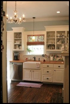 kitchen sink, windows, upper cabinets, wooden counters, wood floors, cream cupboards