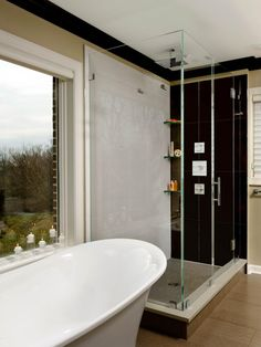 This contemporary master bathroom features a large picture window that offers great natural light and fits seamlessly over a sleek, freestanding tub. The frameless glass shower has a brown accent wall and a rainfall showerhead.