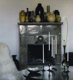 fireplace mantel with green vase and bottle collection
