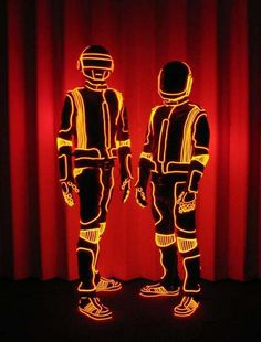 The creator of the EL Wire suits for Daft Punk has written a tutorial on exactly how to stitch the glowing wire into any clothing. Step by step instructions and close up pictures of Daft Punk gear help you along the way. http://www.instructables.com/id/how-to-add-EL-wire-to-a-coat-or-other-garment/
